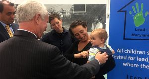 From left, Joseph Manko, principal of Liberty Elementary School; Dr. Howard M. Haft, Maryland's deputy secretary of public health; and Dr. Alexis Boscak and Shana Boscak, holding their son Zoltan, chat Monday during a lead-poisoning awareness campaign held in Baltimore by the Green and Healthy Homes Initiative and state officials, coinciding with National Lead Poisoning Prevention Week. (Bryan P. Sears)