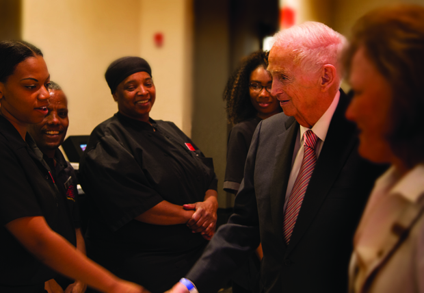 "Brittany Turner, left, a server at The Yard in Baltimore Marriott Inner Harbor at Camden Yards, gets a congratulatory handshake from J. W. ""Bill"" Marriott Jr., the executive chairman and chairman of the board of Marriott International Inc., during the grand opening of BricknFire Pizza Co."