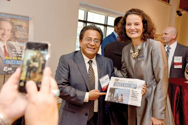 Pedro A. Palomino, left, with Palomino Media Group, shows off a copy of The Daily Record with its publisher, Suzanne Fischer-Huettner. (The Daily Record / Maximilian Franz)