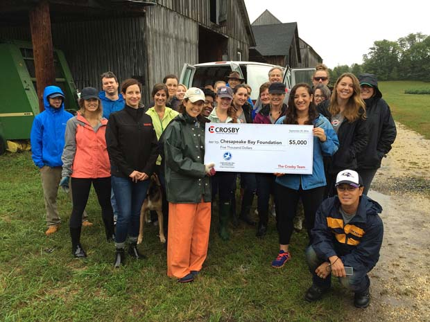 Crosby Marketing Communications employees display a $5,000 check presented to the Clagett Farm in Upper Marlboro during its day of service. (Crosby Marketing Communications photo)