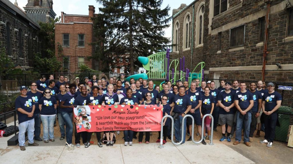 Volunteers celebrate the completion of the playground build at the Family Recovery Program in Baltimore. (Submitted photo)