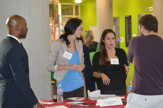 Charlotte Clarke, second from left, and Christina Ochoa talk with attendees as they staff The Saint Ambrose Housing Center table at the Oct. 19 Pro Bono Connection event. (Submitted photo by Elizabeth Grove)