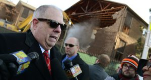 Gov. Larry Hogan speaks to journalists after a news conference about the progress of Project C.O.R.E. as demolition begins in the background to make way for the Madison Park North site, which will house a mixed use innovation center. (The Daily Record / Maximilian Franz)