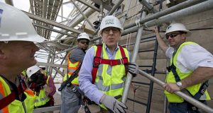 FILE - In this June 2, 2013, file photo, philanthropist David Rubenstein, center, is seen with others at the 491-foot level of the scaffolding which encompasses the Washington Monument in Washington.  (AP Photo/Alex Brandon, File)