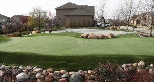 This Monday Nov 28, 2016, photo, shows Eric Marsh's backyard with a golf putting green in Omaha, Neb. Marsh, who lost a lawsuit over the golf putting green, pool, fire cauldrons and other outdoor amenities he added to his suburban property has refused to abide by a court order to remove some of the elements in his sports wonderland. (Megan Smith/Omaha World-Herald via AP)