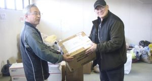 "In this photo provided by Joseph Roginski, taken May 13, 2011, Joseph Roginski, right, holds a package in a storeroom of the Misawa City Hall in Japan, where donations of clothing and supplies were being kept for earthquake relief efforts. He says that while the cost of living is higher in Japan, access to health care is not. ""Things are very expensive here. It is impossible to live off Social Security alone,"" said Roginski, who was stationed in Japan in 1968. ""But health insurance is a major factor in staying here."" The former military language and intelligence specialist said he pays $350 annually to be part of Japan's national health insurance. His policy covers 70 percent of his costs. The rest is covered by a secondary insurance program for retired military personnel. (Joseph Roginski via AP)"