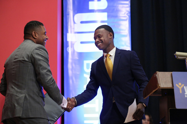 Keynote speaker Calvin G. Butler Jr., left, the CEO of Baltimore Gas & Electric Co., shakes hands with Ike Olumese, a Year Up Baltimore student, during their graduation ceremony at Baltimore City Community College's Fine Arts Theater. (Photo by Jason Putsche Photography)
