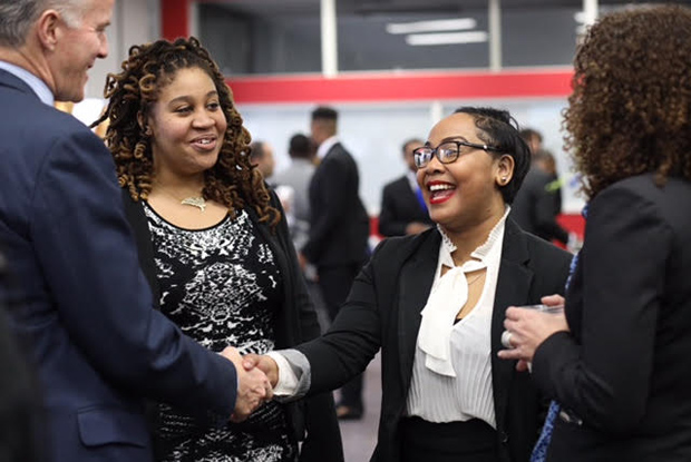 Garrett Moran, left, the national president of Year Up, shakes hands with Tanisha O'Donoghue, who interned with Symantec, as fellow graduate Jazmine Williams, who interned with CareFirst BlueCross BlueShield, looks on during their graduation event. (Photo by Jason Putsche Photography)