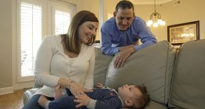 In this Tuesday, Feb. 7, 2017 photo, Lauren Nieves-Taranto, left, and husband Francisco play with their youngest child Nicolas, 4-months, at their home in Windermere, Fla. Nieves-Taranto covered the entire $8,000 bill from the birth of Nicolas last year with his account balance from a health savings account, or HSA. (AP Photo/John Raoux)