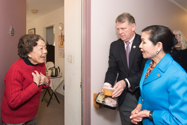 A meals on wheel client, left, receives a delivery from Howard County Executive Allan Kittleman, center, and first lady Yumi Hogan. (Photo by Donovan Eaton)