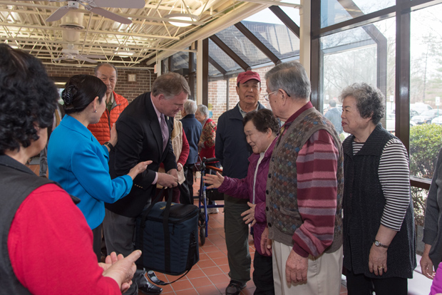 Howard County Executive Allan Kittleman and first lady Yumi Hogan greet residents as they arrive in the lobby of Longwood Apartments in Ellicott City, where they made the first deliveries in Meals on Wheels of Central Maryland's new Korean meal delivery program. (Photo by Donovan Eaton)