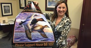 Del. Mary Ann Lisanti, D-Harford, stands in her Annapolis office holding up a poster in support of naming the canvasback duck as Maryland's state waterfowl. (Jake Brodsky/Capital News Service)