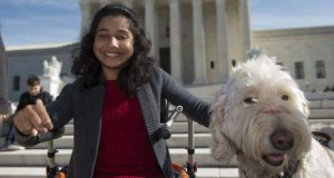 In this Oct. 31, 2016 file photo, Ehlena Fry of Michigan, sits with her service dog Wonder, while speaking to reporters outside the Supreme Court in Washington. The Supreme Court says a lower court should take another look at whether Fry, who has cerebral palsy can sue Michigan school officials over their refusal to let her to bring a service dog to class.  (AP Photo/Molly Riley, File)