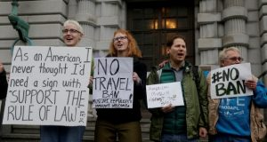 Kay Aull, from left, holds a sign and chants with Beth Kohn, Paul Paz y Mino and Karen Shore outside of the 9th U.S. Circuit Court of Appeals in San Francisco on Tuesday. President Donald Trump's travel ban faced its biggest legal test yet Tuesday as a panel of federal judges prepared to hear arguments from the administration and its opponents about two fundamentally divergent views of the executive branch and the court system. (AP Photo/Jeff Chiu)
