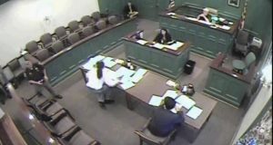 This video still from Charles County Circuit Court in July 2014 shows Delvon L. King, in white shirt, falling after a deputy sheriff, far leftm activated the shock cuff on King's leg on the orders of Judge Robert C. Nalley. King filed a $5 million lawsuit against Nalley Monday in U.S. District Court. (Charles County Circuit Court via AP)