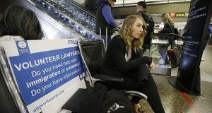 Asti Gallina, a volunteer law student from the University of Washington, sits at a station near where passengers arrive on international flights at Seattle-Tacoma International Airport, Tuesday, Feb. 28, 2017, in Seattle. Gallina was volunteering with the group Airport Lawyer, which also offers a secure website and mobile phone app that alerts volunteer lawyers to ensure travelers make it through customs without trouble. Airport officials and civil rights lawyers around the country are getting ready for President Donald Trump's new travel ban, which is expected to be released as soon as Wednesday. (AP Photo/Ted S. Warren)
