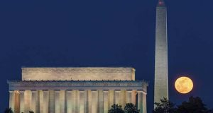 The full moon rises behind the Lincoln Memorial and Washington Monument on the last clear night before the arrival of the approaching winter storm in Washington, Sunday, March 12, 2017. (AP Photo/J. David Ake)