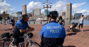 Two Baltimore police bike unit officers watch over the Inner Harbor promenade by the Maryland Science Center in 2017. (Maximilian Franz/The Daily Record)