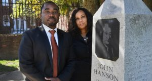 Christian Addison and his cousin Tanya Lyle pose with a monument (the monument is near the MGM National Harbor Casino) that honors John Hanson. John Hanson was a merchant and public official from Maryland during the era of the American Revolution. They are distant relatives of Hanson. Addison and Lyle are descendants of a family that owned property near the MGM National Harbor Casino and are suing to prevent the developer from removing a family cemetery. CUST CREDIT: (The Washington Post photo by Michael S. Williamson.)