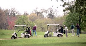 Four Golfers tee off in two carts at Clifton Park golf course in Baltimore. (The Daily Record / Maximilian Franz)