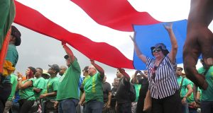 People carry a large Puerto Rican flag as they protest looming austerity measures amid an economic crisis and demand an audit on the island's debt to identify those responsible, in San Juan, Puerto Rico, Monday, May 1, 2017. Puerto Rico is preparing to cut public employee benefits, increase tax revenue, hike water rates and privatize government operations, among other things. (AP Photo/Danica Coto)