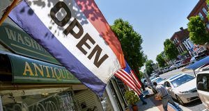 An 'Open' flag flaps in the breeze outside of Washington Street Books on Washington Street in Havre de Grace, MD. (The Daily Record/Maximilian Franz)