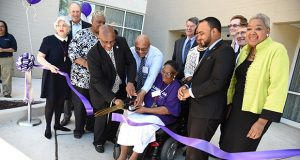 Louise Baynard, Resident Council President at The Allendale apartments, cuts the ribbon with a group of officials at the Allendale grand re-opening celebration at 3600 West Franklin Street, a 164 unit, 12-story, affordable housing apartment building. Originally built in 1985, for seniors and disabled adults, now re-developed in collaboration with Baltimore Affordable Housing Development, Inc., an affiliate of the Housing Authority of Baltimore City, under HUD's new Rental Assistance Demonstration Program or RAD. (Maximilian Franz/The Daily Record)