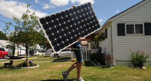 7.2.10- BALTIMORE, MD- Lila Holzman, Project Lead from Astrum Solar, a solar installation firm in Maryland, carrying a solar panel accross the lawn of Jeff and Michele Manning. Photo by Maximilian Franz/ The Daily Record