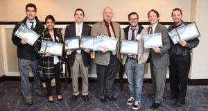 Staff members of The Daily Record hold awards at the Maryland Delaware District of Columbia Press Association's 2016 Editorial Awards, Friday at the DoubleTree by Hilton hotel in Annapolis. Pictured are, from left, Jason Whong, digital editor; Anamika Roy, reporter; Danny Jacobs, legal editor; Bryan P. Sears, reporter; Adam Bednar, reporter; Steve Lash, reporter; and Maximilian Franz, photographer.