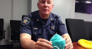This May 25, 2017 photo shows Harford County Major John R. Simpson is seen at the Harford County Sheriff's Office, MD., holding up elements of a protective suit that the sheriff's office is now providing to deputies sent to crime scenes involving heroin and synthetic opioids. After a deputy accidentally overdosed while at a drug scene, the department rushed to procure protective gear and establish protocols for officers responding to drug scenes. (AP Photo/Juliet Linderman)