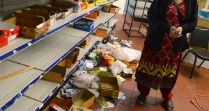A woman surveys the riot damage April 28, 2015 in her grocery store on the 300 Block of North Charles Street. (The Daily Record / Maximilian Franz)
