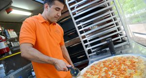 Joey Vanoni, owner of the Pizza di Joey food truck, slices a buffalo chicken pizza in his mobile kitchen. Vanoni is suing Baltimore city over a rule that prevents him from setting up within 300 feet of a brick-and-mortar restaurant that specializes in pizza. (Maximilian Franz/File photo)