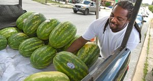 6-27-17 BALTIMORE, MD- Donald Savoy, 40-year-old third-generation Arabber from Baltimore, picks out a watermelon from the back of his truck for a customer on side of 28th street in Remington. He as been doing his part to keep the family tradition alive for the past 30 years. (The Daily Record/Maximilian Franz)