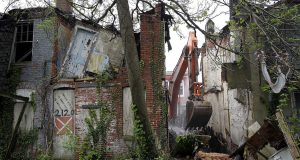 In this April 26, 2017 photo, an abandoned row house is demolished in Baltimore as part of a blight-fighting initiative called Project CORE. (AP Photo/Patrick Semansky)