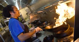 Honeygrow, one of the more recent entries in the fast casual-restaurant sector, has two locations in Baltimore. Wok chef Hideo Williams cooks at the 3212 St. Paul St. restaurant. (The Daily Record/Maximilian Franz)