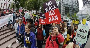 In this May 15, 2017 file photo, protesters wave signs and chant during a demonstration against President Donald Trump's revised travel ban, outside a federal courthouse in Seattle. (AP Photo/Ted S. Warren, File)