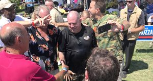 Gov. Larry Hogan, besieged by well-wishers, poured water on his shirt to cool off in the blazing heat.