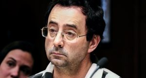 In this Feb. 17, 2017, file photo, Dr. Larry Nassar listens to testimony of a witness during a preliminary hearing, in Lansing, Mich. Nassar, a former Michigan State University and USA Gymnastics sports doctor, is taking a step toward resolving one of four criminal cases against him in Michigan. Nassar is due in federal court Tuesday, July 11, to plead guilty to child pornography charges. It's separate from sexual assault charges involving women and girls who said they were molested when they sought treatment for gymnastics injuries. (Robert Killips/Lansing State Journal via AP, File)