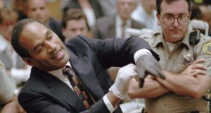In this June 15, 1995 file photo, O.J. Simpson, left, grimaces as he tries on one of the leather gloves prosecutors say he wore the night his ex-wife Nicole Brown Simpson and Ron Goldman were murdered in a Los Angeles courtroom. Simpson, the former football star, TV pitchman and now Nevada prison inmate, will have a lot going for him when he appears before state parole board members Thursday, seeking his release after more than eight years for an ill-fated bid to retrieve sports memorabilia. (AP Photo/Sam Mircovich, Pool, File)