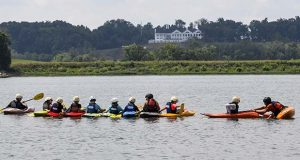 With the Trump National Golf Club clubhouse in the background, Camp Calleva kayak instructor Steve McKone helps one of his campers while teaching a lesson on the Potomac River during a camp session on July 17, 2017. MUST CREDIT: Washington Post photo by Toni L. Sandys.