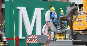 Sign workers were fastening the M&T logo onto the green panels by the Ray Lewis statue by the Ravens walk which will soongreet thousands of fans as the Ravens pre-season kicks off. (The Daily Record/Maximilian Franz)