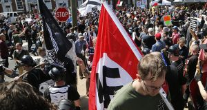 A white supremacist carries a Nazi flag into Emancipation Park in Charlottesville, Va., on Aug. 12. Such a display in the workplace would be swiftly addressed. Outside of the office, however, the relationship between corporate codes of conduct and hateful politics is less straightforward. (AP photo/Steve Helber)