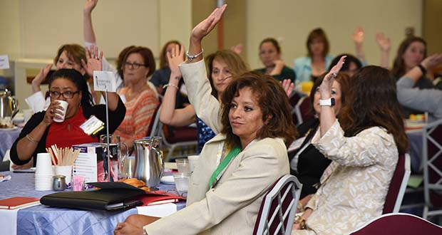A group of women among the nearly 150 in attendance raise their hands during a presentation. (The Daily Record / Maximilian Franz)