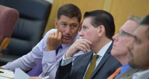 Maryland Medical Cannabis Commission Chairman Brian P. Lopez, left, and Executive Director Patrick Jameson talk as public comment is given on potentially adding 15 processor licenses. (Bryan P. Sears)