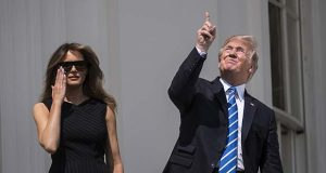 President Donald Trump looks up toward the solar eclipse, with first lady Melania Trump by his side, from a balcony at the White House. MUST (Washington Post photo by Jabin Botsford)