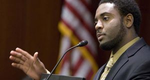 "FILE - In this Nov. 5, 2009 file photo, Reginald Dwayne Betts, writing workshop program director, speaks during a school forum on Capitol Hill in Washington. Betts, a convicted felon who graduated from Yale Law School and won acclaim as a poet is being asked by a Connecticut committee to prove his ""good moral character"" before he is allowed to practice law. Like most states, Connecticut does not prohibit felons from becoming attorneys, but a felony conviction creates a presumption that the applicant lacks ""good moral character and/or fitness to practice law."" Such applicants must prove otherwise by ""clear and convincing evidence.""(AP Photo/Alex Brandon, File)"