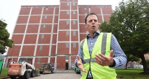 Andrew Beebe, head of the Guinness Open Gate Brewery & Barrel House gestures in front of the building that will house the future test tap room during a tour of the campus on Wednesday. (The Daily Record / Maximilian Franz)