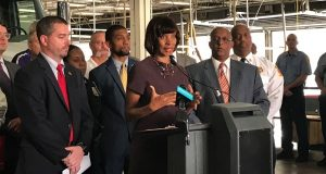 """Mayor Catherine Pugh, surrounded by Councilman Eric Costello, Councilman Brandon Scott, and City Council President Bernard C. """"Jack"""" Young discusses a proposal to provide city police officers and firefighters a $2,500 tax credit to purchase a home in Baltimore. (Adam Bednar/The Daily Record)"""