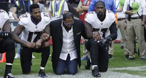In this Sunday Sept. 24, 2017, file photo, Baltimore Ravens wide receiver Mike Wallace, from left, former player Ray Lewis and inside linebacker C.J. Mosley lock arms and kneel down during the playing of the U.S. national anthem before an NFL football game against the Jacksonville Jaguars at Wembley Stadium in London. People have signed an online petition asking for the removal of a statute of Lewis after he joined other NFL players kneeling during the national anthem. (AP Photo/Matt Dunham, File)