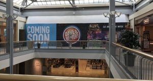 """A """"coming soon"""" sign is shown on the entrance to a new Dave & Buster's restaurant coming to White Marsh Mall. The restaurant is expecting to hire for 230 positions before its opening in December. (File courtesy ocmercj via Flickr)"""